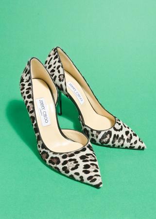 london, england, 05/05/2018, jimmy choo designer high heeled women shoes. leopard print pattern design on a green studio background. pointy heel stilettos.