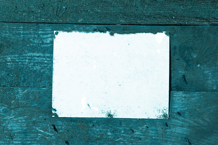 A blank Rustic weathered beach warning sign on a wooden sea defence wall. Aqua blue and empty mock sign perfect for text and graphics. Empty rectangle.