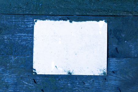A blank Rustic weathered beach warning sign on a wooden sea defence wall.  blue and empty mock sign perfect for text and graphics. Empty rectangle.