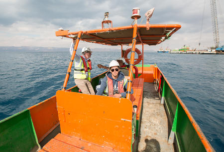 Aqaba, Jordan, 10/10/2015, An orange and green tug boat driver, driving and transporting men in plastic safety work hats, across the dead sea red sea in a metal boat. amongst the jetty construction site. Sajtókép