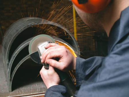 A man working with a grinder in a factory, creating sparks. metal working apparent angle grinding metal and steel parts. matte dark photography.