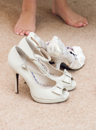 A bride putting on her wedding shoes in preparation for the wedding ceremony. Soft delicate white and cream colours. feet and shoes on a textured carpet. Stock fotó