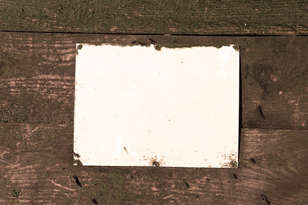 A blank Rustic weathered beach warning sign on a wooden sea defence wall. sepia tones and empty mock sign perfect for text and graphics. Empty rectangle.