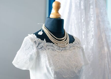 Vintage second hand beautiful white clean lace dress and large pearl necklace on a retro vintage dressmakers mannequin stand. flea market and thrift store fashion.