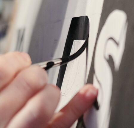 An artists hand with a paint brush painting retro letters and typography graphics. Standard-Bild - 129484769