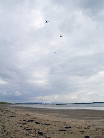 Rhosneigr, wales, 05052018 Royal airforce RAF fighter jets flying over the beach and preparing to land on the runway close to the beach. Fighter jets in a moody atmospheric dramatic cloudy sky.