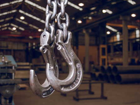 london, england, 05/05/2018  Steel and iron industrial meat hooks hanging empty in a dark factory in england. Stock fotó - 129476448