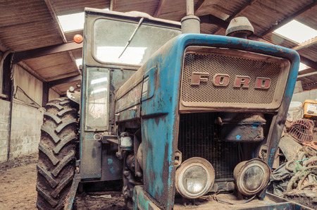 lancashire, England, 06/06/2016, An old abandoned vintage retro Ford tractor, forgotten and rusting in an old farm shed. Foto de archivo - 129476563