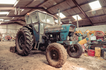 lancashire, England, 06/06/2016, An old abandoned vintage retro Ford tractor, forgotten and rusting in an old farm shed. Foto de archivo - 129476708
