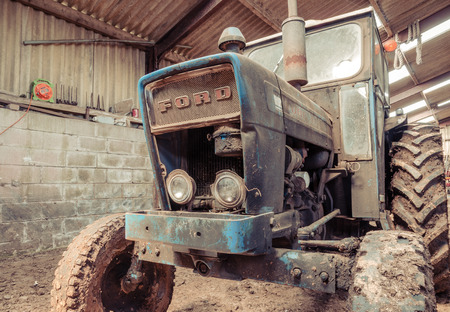 lancashire, England, 06/06/2016, An old abandoned vintage retro Ford tractor, forgotten and rusting in an old farm shed. Foto de archivo - 129476719