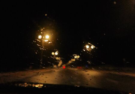 Abstract painterly rain drops on a car window with vibrant city and street lights out of focus in the background. Tired and drunk driving in wet and rainy conditions. safe driving.