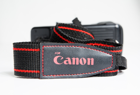 london, england, 05052018 A official canon camera strap for  a dslr or analog sir film camera. Carrying photographic equipment on the shoulder. Black and red strap for single lens reflex camera body.