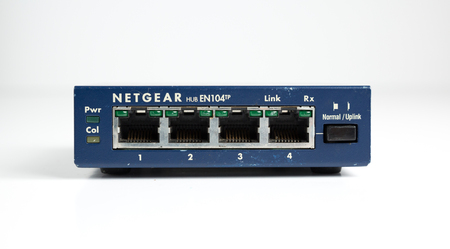 london, england, 05052019 A retro outdated analogue netgear ethernet hub for computers and network servers. Ethernet wires for stronger internet connection. digital data transmission. Redactioneel