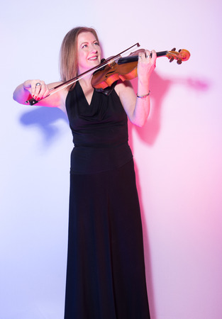 london, england, 05052019 A woman playing the violin full body against a white background. Neon colour light up the shadow areas. happy musician smiling playing instrument. healthy hobby