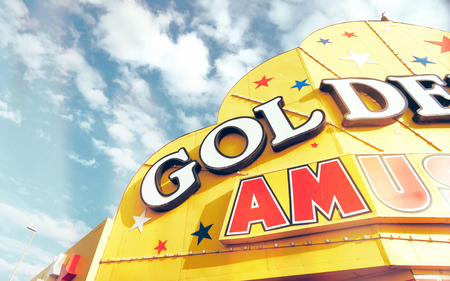 A bright yellow vintage gambling arcade sign on the seafront in the seaside town of blackpool england, against a vivid blue sky. Golden yellows and red. happy memories from childhood.