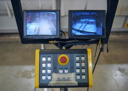 automated industrial factory control desk screens and buttons overseeing the automated machinery where humans are no longer needed. computers and robot controls making more money for corporations.