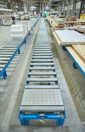 An empty industrial roller conveyor belt in a fully automated factory. roller conveyor to easily move heavy industrial goods around without the need for humans.future of industrial manufacture. Фото со стока