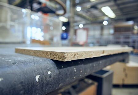 chipboard on an industrial roller conveyor belt in a fully automated factory. roller conveyor to easily move heavy industrial goods around without the need for humans.future of industrial manufacture.