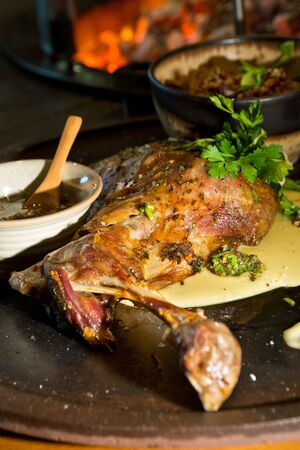 Delicious free range roasted goat shoulder served on a rustic metal plate by a hot open coal fire. Served with fresh parsley. Stock Photo