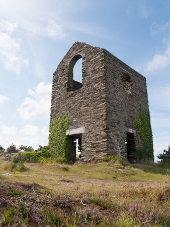 An old stone building ruin in the middle of the english countryside.