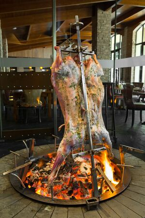 Delicious organic Whole Roasted goat on a Spit roast rack over a hot open Fire, cooking slowly. 版權商用圖片