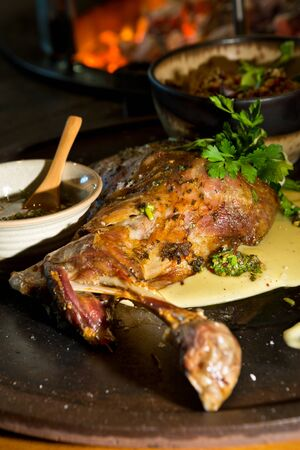 Delicious free range roasted goat shoulder served on a rustic metal plate by a hot open coal fire. Served with fresh parsley. 版權商用圖片