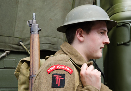 Yorkshire, England, 05/15/2015, Young british soldier with a tin hat and rifle, Howarth 1940s weekend