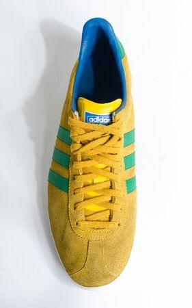 london, england, 05/05/2018  Adidas Gazelle Mustard Gold & Green Stripe Trainers vintage sneaker trainers. yellow suede adidas trainers, stylish retro football street fashion. famous three stripes