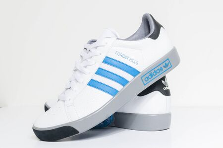 london, england, 05/05/2018  Adidas Forest Hills White grey and blue vintage sneaker trainers. Blue stripe adidas trainers, stylish retro football street fashion. famous three stripes