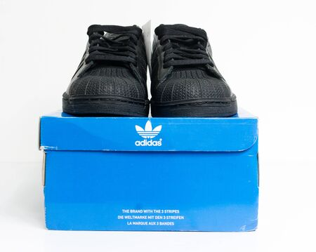 london, england, 05/05/2018 adidas superstar shell toe originals hip hop style vintage sneaker trainers. all black adidas superstar trainers, stylish retro  new york street fashion. 版權商用圖片