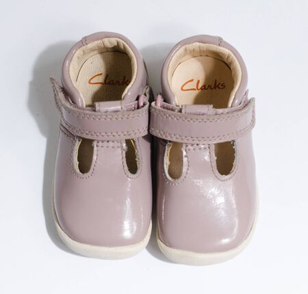 london, england, 05/05/2019 cute little vintage retro pink baby dolly shoes, isolated on a white studio background.  Tiny baby sneakers for a baby shower. Babies feet grow fast.