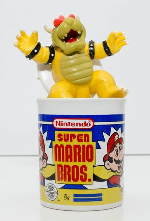 london, england, 05052018 a super mario official nintendo 1990s super mario bros mug coffee cup and bowser toy isolated on a white background. official merchandise. Sajtókép