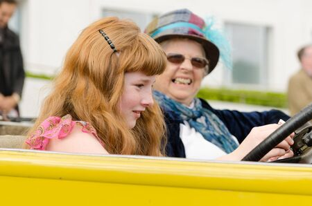 london, england, 10112018 An old lady and a young girl with red hair driving in an old vintage car vehicle. Dressed in nostalgic vintage clothing and unusual fashion sense. 新聞圖片