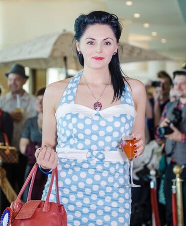 morecambe, England, 05052017, A stylish polka dot vintage fashionable women wearing a blue retro dress, fancy dress cosplay. beautiful, pinup era style fashion girl drinking.