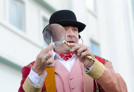 london, england, 15032019 A flea circus street performer with a magnifying glass entertaining children on the city streets. Traditional flea circus ringmaster funny man. 新聞圖片
