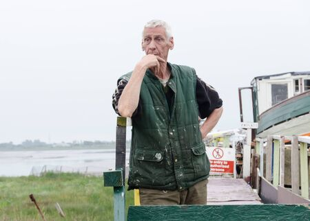 lancashire, england, 14042019 A local old traditional european fisherman, standing by his boat that is moored up on a jetty by a river. Local seaman fishing industry.