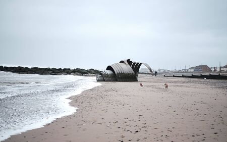 Huge metal sea shell conch sculpture on the beach at sunset. barnacles and seaweed have attached to the metal hull. Standard-Bild