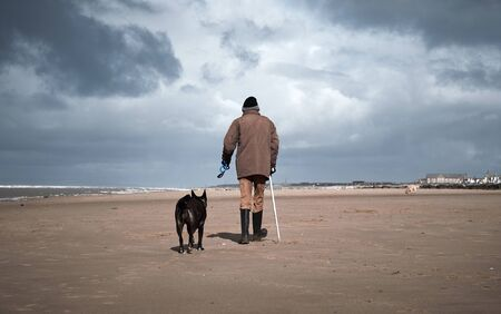 A retired old man with a walking stick, walking his dog on a beach. Dogs are mens best friend and loyal companions for older people who are alone. Humans and animals together. Standard-Bild