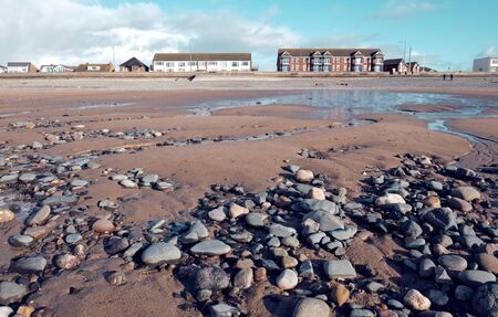 Beautiful sunny winters day on a british beach, with sand ripples, beach stones and the sky reflecting in a water pool.