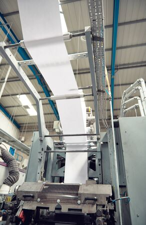 A toilet paper making machine, producing toilet and bathroom paper rolls due to Corona virus panic buying.  Paper and tissue manufacturers factory and engineered machinery.