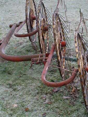 a rusty old antique filed plough in a misty cold damp winters filed and paddock. winter dead crops, ice and frozen farm equipment. frosty and misty air.