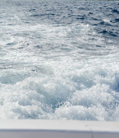Water splashes and ripples from behind a boat in a blue ocean. boat motion and movement, bubbling splashing water surface. progressive moving forward and leaving behind,