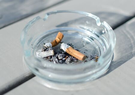 A filthy dirty smoking cigarette ash tray. smoking kills and ruins lives. smelly toxic habits that cause cancer disease. nicotine and tar industry harming human lung and heart health. Stock Photo