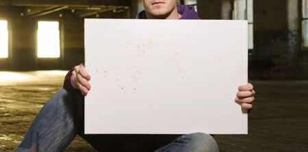 A white male holding an empty blank protest billboard in an urban warehouse setting. People power, power to the people. blank mock board for compositing.