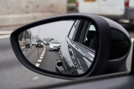 A rear view of a highway motorway, seen through the glass of a rear view mirror on an automobile car. Gloomy polluted city sky and vehicle backdrop. Driving a car fast on the city streets. Stock Photo
