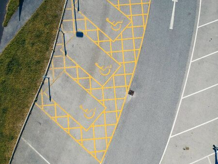 parking bay and disable parking bays from above photographed in an urban setting with a drone. lines and pattern street road markings. straight lines and geometric. drone photography above