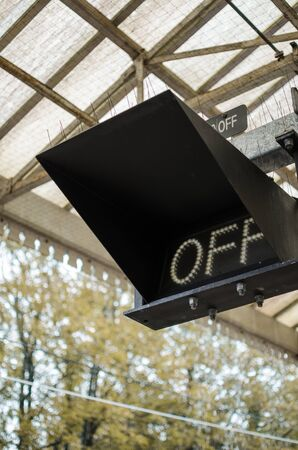 An off electrical sign railway signal box in a railway train station on the platform. Signals to control rail traffic and keeping the rail road safe. Stock Photo