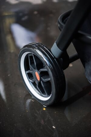 A baby pram stroller pushchair wheel tyre,  in a wet rainy dirty city sidewalk pavement environment. City strollers, and fashionable baby pram accessories for city living parents. modern parent hood. Banco de Imagens