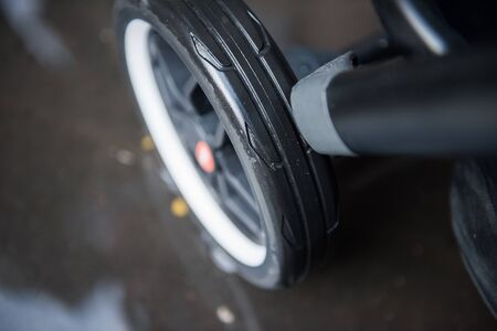 A baby pram stroller pushchair wheel tyre, in a wet rainy dirty city sidewalk pavement environment. City strollers, and fashionable baby pram accessories for city living parents. modern parent hood.