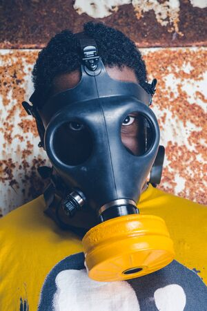 A black male with a military grade gas mask to protect himself from the corona virus covid19 pandemic. Face mask used to prevent the spread of the virus. Mandatory face coverings.